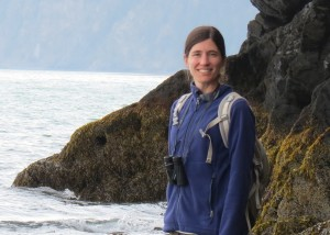 Woman posing with a smile in front of shore by rocks