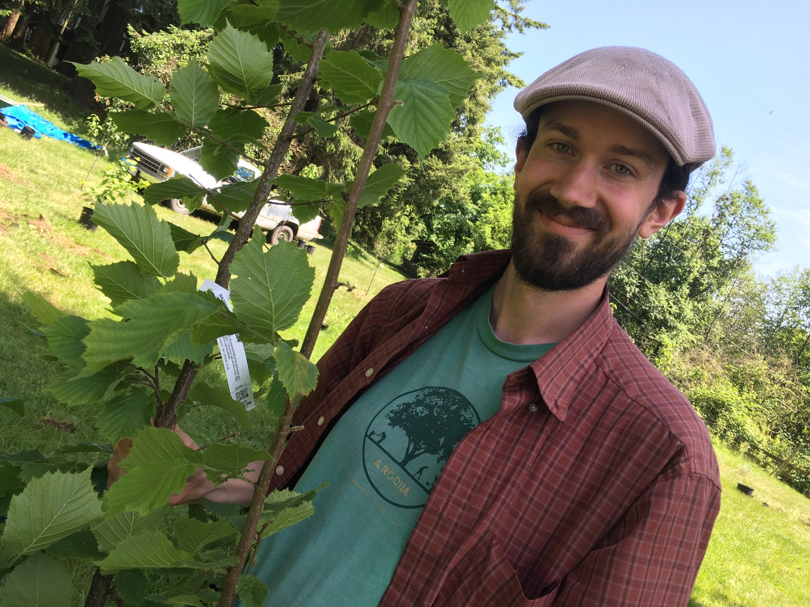 Tim Friesen poses next to tree in orchard