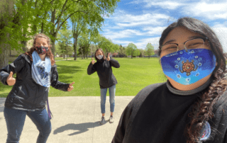 3 young women (Kari, Lauren and Madison), standing staggered and wearing masks.