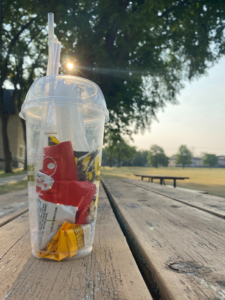 Clear plastic to-go cup filled with plastic waste, placed on a picnic table in front of trees,