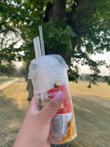 A hand holding a clear to-go cup filled with plastic waste, with trees in the background.