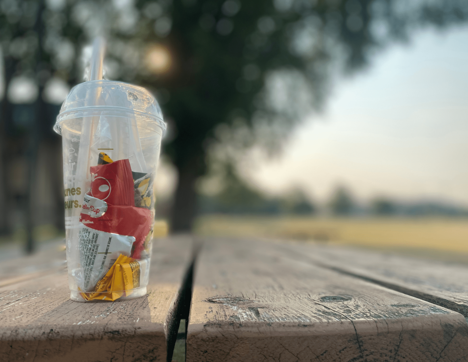 A clear to-go cup, filled with plastic wrappers and waste, sitting on top of a picnic table. Blurry trees in the background.